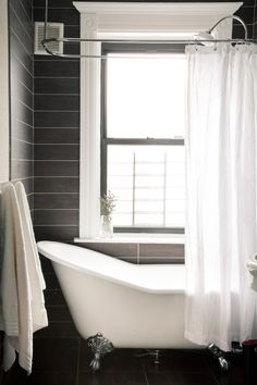Note white window and bath against dark walls and floor