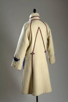 Coat of white wool, with patch pockets of blue felt trimmed with red and silver leather and flowers of red and green. Coat buttons right over left, Poiret, 1923