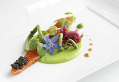 At Chez TJ, wild king salmon is served with fiddlehead fern, English peas and sauerkraut.