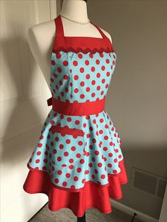 Flirty womens apron with fitted bodice and full skirts in pinup turquoise and red polka dots.