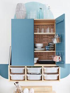 """Der blau gestrichene Schrank wird optisch durch Muster an der Wand ergänzt: Ein Halbkreis rundet den Schrank oberhalb ab und rahmt die Abstellfläche auf dem Schrank ein. Das Regal unterhalb des Schranks wird durch blaue """"Zierleisten"""" an der Wand erweitert. Die Rückseite im Schrank ist mit Papier beklebt. Und durch Körbe, die mit Haken an der Innenseite der Tür angebracht sind, wird zusätzlicher Stauraum geschaffen."""
