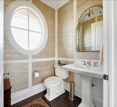 This powder room has grasscloth wallpaper on walls. The mirror is from Uttermost, Gella #12595