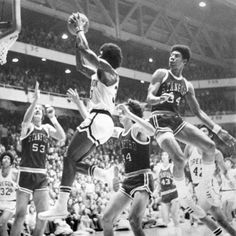 Black and white photo of University of Oregon basketball player Ronnie Lee soaring to the basket during a game played against Stanford at McArthur Court on February 23, 1974 and won by the Ducks 72-71. Also visible are Ducks Stu Jackson (#32) and Greg Ballard (#42). ©University of Oregon Libraries - Special Collections and University Archives