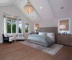 Master Bedroom. This relaxing master bedroom features custom upholstered bed with tufting and nail head trim, chevron nightstands and Jaipur rug, The vaulted ceiling features stained and paint grade beams. Patterson Custom Homes. Interiors by Trish Steele of Churchill Design.