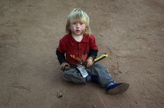 Renier Christian plays with a hatchet while sitting in the dirt of a White South African squatter camp on June 7, 2010 in Krugersdorp, South Africa. The local municipality tried to evict the squatters from the land last year to make room for a fan park for the soccer World Cup, but a judge ruled that they could remain. The government then cut off the electricity to the camp. Many poor whites living there blame affirmative action programs launched by the ANC government for their unemployment…