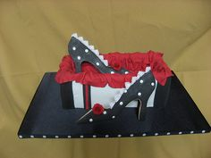 Shoe therapy ...The box and shoes are cookie and the tissue paper and roses are gumpaste.