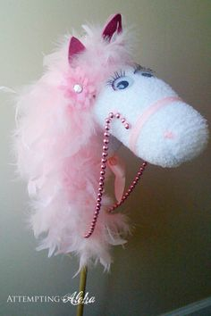 Possibly the Most Glamorous Hobby Horse Ever - for a little girl ... start with a cheap stick horse from a dollar store, add a feather boa mane, pink bead reins [Christmas bead garland], a pink fake flower and voila!  All this gal needs is a name.