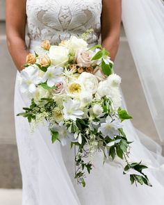 """Cream peonies were just one of the soft blooms in this overgrown bridal bouquet. It also featured cream O'hara garden roses, quicksand roses, sahara spray roses, bay leave foliage, clematis, olive foliage, dusty miller, trailing jasmine, cream ranunculus, and polo garden roses—all bound with dusty gray, champagne, and ivory ribbons. """"Sitting down and meeting with Fleur's Kelly Marie for my own wedding is something I've been dying to do since we first started working together years ago,"""" the…"""