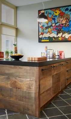 A beautiful wooden kitchen. A great combination of rustic and modern. Love the bright picture in the background!