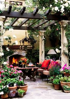 Fireplace, printed table, chairs with colorful cushion, potted plants, hanging chandelier