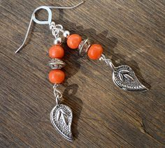 Tibetan stamped fine-silver leaves dangle from a tidy stack of coral jade rounds & silver (filled?) beads; Sterling silver ear wires & findings.
