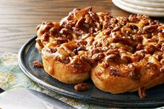 Refrigerated crescent dough is topped with sugar, cinnamon, pecans and raisins, rolled up, sliced and baked in gooey caramel for a breakfast treat.