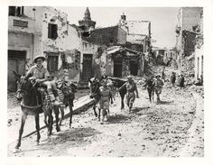 1943. Allied soldiers lead pack mules through the streets of Adrano, Sicily, after capture of the town.