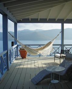 Hammock in corner of  a wrap around porch on a lake.