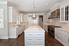 Fantastic kitchen features white shaker cabinets paired with white quartz countertops and a white ...