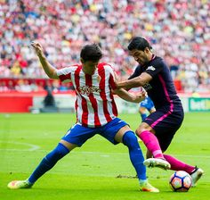 Luis Suarez of FC Barcelona duels for the ball with Jorge Mere of Real Sporting de Gijon during the La Liga match between Real Sporting de Gijon and...