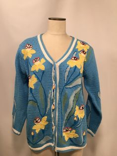 Ladies medium sweater cardigan. Storybook Knits. Blue with yellow Daffodils flowers on front, back and sleeves. Hidden buttons. 55% ramie 45% cotton. Hand wash. Please review all measurements and pictures carefully.