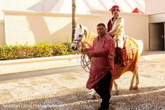 Indian groom riding the baraat horse. in Cancun, Mexico Indian Wedding by Jonathan Cossu Photographer | Maharani Weddings