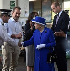 Britain's Queen Elizabeth and Prince William meet emergency workers near the scene of the ...