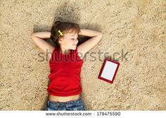 dreaming smiling cute little girl lying on the sand with a tablet computer. child on vacation