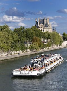 Sightseeing boat on river Seine to Louvre museum
