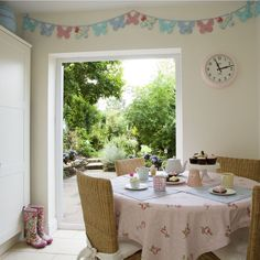 Pastel-coloured bunting, a floral tablecloth and simple furniture lends this pretty dining room an elegant, country atmosphere. Create this look at home with pastel accessories!