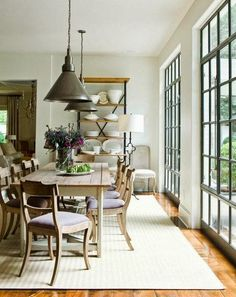 Design by Suzanne Kasler ... Hardwood floors, barn-style light fixtures, black window frames & muntins, farmhouse table