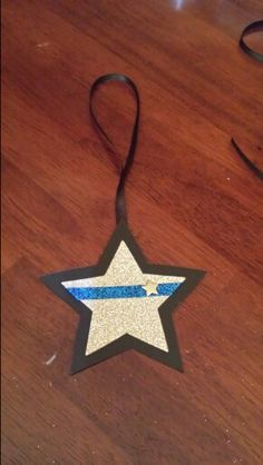 Thin Blue Line Police Officer or Sheriff ornament gift. Products purchased from Michaels.  Glitter sticker star. Blue glitter tape cut to fit. Black star was cut from circle chalk board paper. Small silver star clips pushed through a hole punch. Although tape and star are stickers,  I had to super glue everything. The back is stamped with officer initials,  year and badge number. Small black ribbon superglued to back to hang. I placed in envelopes to deliver.