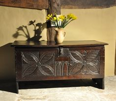 A EARLY 16TH CENTURY ENGLISH CARVED OAK PLANK CHEST-THE SINGLE PLANK TOP ABOVE A FRONT CARVED WITH LEAF AND BUD DECORATION AND CENTRED BY TWO GOTHIC ARCHES.