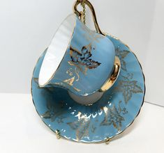 Begin your day with an elegant cup of steeping tea. This elegant antique tea cup and saucer is by Sutherland Fine Bone China of Staffordshire, England. The golden leaves add to its charm. It is a warm, medium delightful blue. Sutherland was one of the famous Staffordshire potteries.