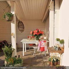 Diese Gartennische mit Loggia-Charakter wurde mit einem weißen Gartentisch und Gartenstühlen eingerichtet. Die Holzverkleidung und die eingetopften Blumen verleihen…