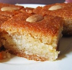 Basbousa is a sweet semolina cake soaked in syrup. Ingredients: cup butter – unsalted cup sugar 1 tspn vanilla essence 2 eggs 2 cups fine semolina (suji) 1 tspn baking powder tspn soda-bicarbonate cup plain or vanilla-flavored yogurt Egyptian Desserts, Egyptian Food, Egyptian Recipes, Just Desserts, Delicious Desserts, Dessert Recipes, Yummy Food, Middle East Food, Middle Eastern Desserts