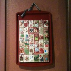 Christmas count down advent calendar. Made using spray painted cookie sheet. Decorated matchbook covers ( to place goodies in). Magnets hot glued to back of boxes. Scrapbooking paper and accents used for decoration.  6 rows horizontally , 6 columns of matchboxes leaving some blank for decor only.