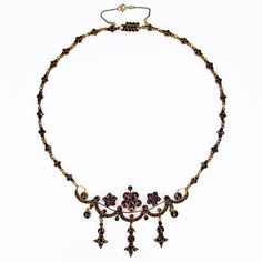 feminine garland of garnets in the Bohemian garnet jewelry style so popular in the Victorian period takes shape in this early 20th Century necklace.