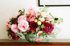 petal pink and warm fuschia arrangement of hollyhock, roses, orchids, dahlias and apples by Tulipina