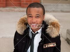 man in winter coat smiles - Close shot of a young man wearing a winter jacket and smiling.