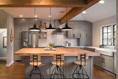 Stylish townhouse kitchen in gray and white with a wooden countertop for the island [Design: Four Brothers LLC]