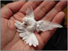 Paper hummingbird sculpture by Cheong-ah Hwang. She creates sculptures and scenes by folding paper and placing it in layers.