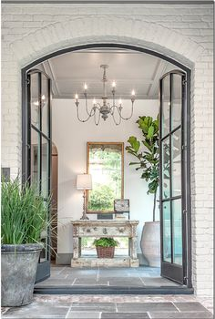 From Cote De Texas ~ Arched Steel Double Doors and Stone Floor inside and out!