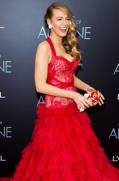 Blake Lively wears a red lace dress paired with an goldfish crystal clutch