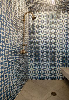 incredible patterned tile shower.  love the blue and white with concrete floor and brass fixtures.