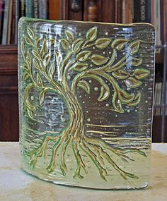 This pale green curved fused glass piece enhances a candle in any room. The embossed tree image is kiln formed into the back of the glass. The leaves, trunk and branches are hand painted with a golden metallic finish which shimmers when lit from the front, and is opaque when lit from the back. The piece is free standing with an elliptical form which makes the tree image visible from multiple angles. This work has been kiln fired twice: once to create the tree embossing and again, after…
