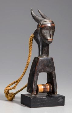 Africa | Heddle pulley from the Guro people of Ivory Coast | Wood, metal and fiber | 20th century
