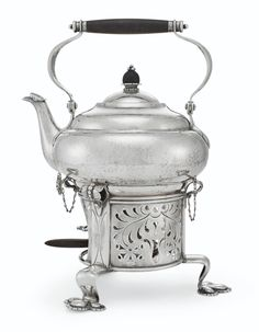 Designed by Georg Jensen in 1913, of squat circular form, swing handle with ebony rod, the cover centered by an ebony bud finial, the cylindrical stand pierced with foliage and raised on three trefid feet, with a removable spirit lamp with ebony handle, marked to underside of kettle and burner121⁄4 in. (31 cm.) high49 oz. 2 dwt. (1,527 gr.) gross weight Elegant Dining, Clay Pots, Vintage Silver, Copenhagen, Kettle, Danish, Pewter, Tea Party, Ceramics