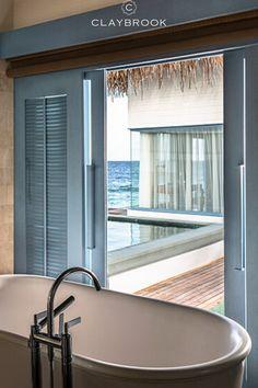 A beautiful hotel bathroom with a view. The Raffles Resort Maldives features beautiful soaking tubs from Claybrook Interiors. #maldiveshotels #bathtub #hotelbathroom