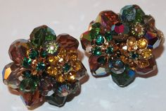 """They are goldtone with beautiful clusters of green and yellow rhinestone rosettes and aurora borealis crystal beads. They are signed """"Vendome"""" on the fold back clips with screws. They are missing one yellow rhinestone in one of the flowers. 