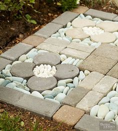 """Careful and artful arrangement of concrete bricks in different shapes and smooth river rocks in various hues form an inexpensive flowered """"rug"""" for the garden. All the materials are readily available at home and garden centers, proving that clever design need not have a hefty price tag."""