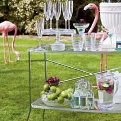 Eclectic Garden Party...trolley is filled with fancy glassware, while giant flamingo ornaments are stationed in the garden.