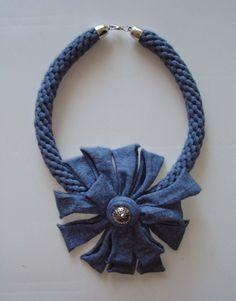 Collar azul con motivo floral, aplique y cierre metálico en color plata.