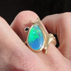 I made this ring from 14k yellow gold; it was inspired by the Caribbean blue hue of the opal, and features a coral branch motif.  I added a small black diamond that perches on the edge of the bezel.
